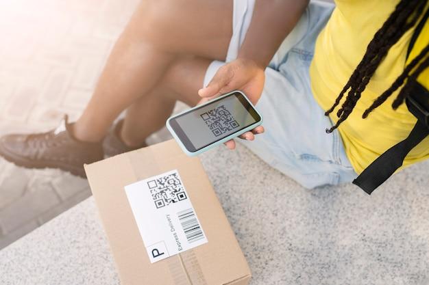 Hand van pakketbezorger, met qr-code