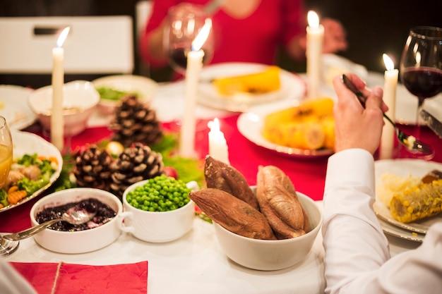 Hand van persoon die bij feestelijke lijst eet