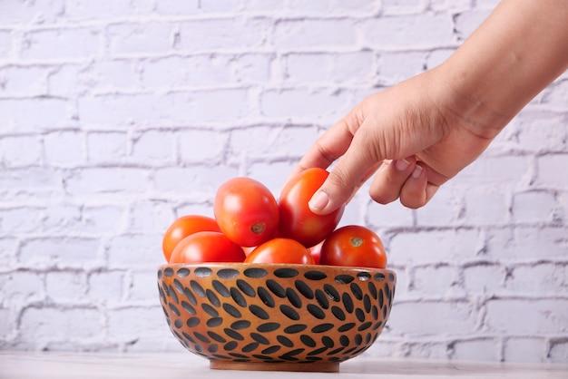 Hand van persoon tomaten uit een kom plukken