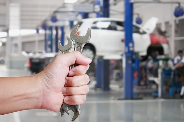 Hand van professionele automonteur met moersleutel, autoreparatieservice