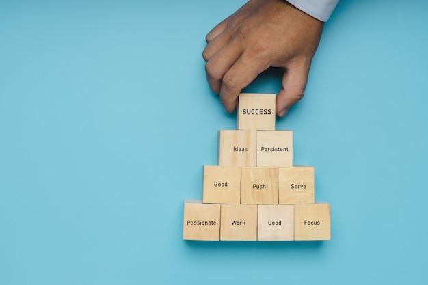Hand van professionele zakenman zet houtblokstap naar succes op zachte blauwe achtergrond, idee en hoe je prestatieconcept kunt krijgen
