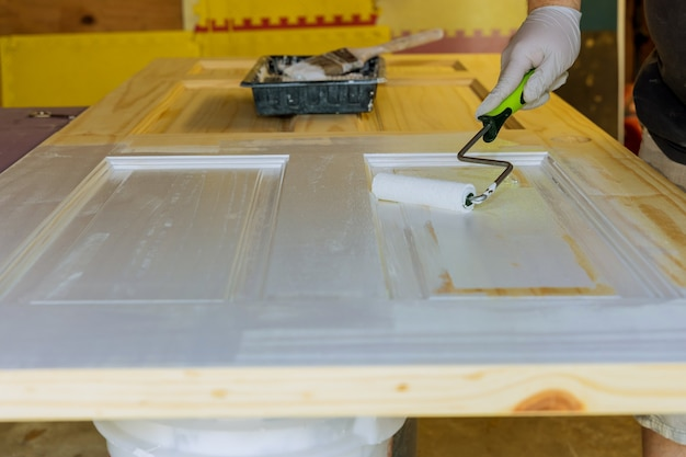 Hand van reparateur met handschoenen van het schilderen van deuren met handroller in een nieuw huis