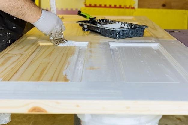 Hand van reparateur schilder met handschoenen met verf houten voordeur met penseel in een nieuw huis