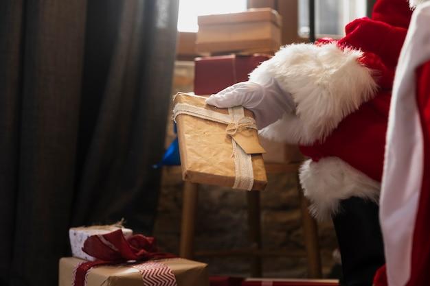 Hand van santa die een kerstmisgift houdt