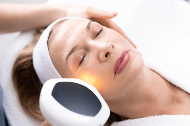 Hand van schoonheidsspecialiste met laserhandvat op het gezicht van volwassen vrouwen tijdens het maken van laser huidvernieuwing, bovenaanzicht