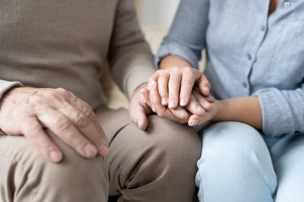 Hand van senior man in vrijetijdskleding tussen die van zijn aanhankelijke jonge dochter terwijl beiden dicht bij elkaar zitten