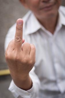 Hand van senior oude man die onbeleefd middelvinger geeft