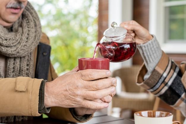 Hand van senior vrouw met theepot die kruidenthee giet in keramische mok die door haar man boven tafel wordt vastgehouden tijdens het ontbijt bij landhuis