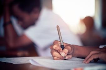 Hand van student neemt examen en schrijft antwoord in klaslokaal