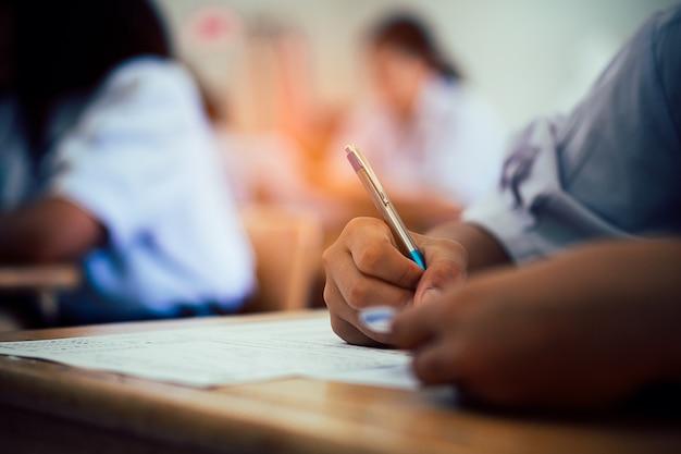 Hand van studenten die examen met spanning in klaslokaal nemen