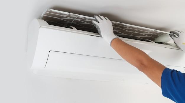 Hand van technicus het schoonmaken airconditioner binnenshuis