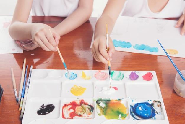 Hand van twee schoolmeisjes gebruik penseel onderwijs concept