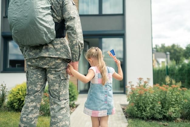 Hand van vader. leuk meisje dat een zomerjurk draagt en de hand van haar vader vasthoudt die in de strijdkrachten dient