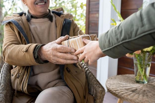 Hand van vrolijke grootvader in warme vrijetijdskleding zittend in een fauteuil bij een kleine tafel en verjaardagsverrassing in geschenkdoos doorgeven aan zijn kleinzoon door huis