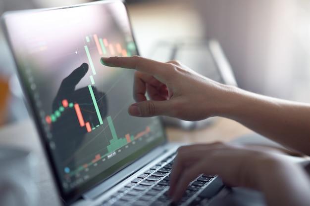Hand van vrouw controleert bitcoin-prijsgrafiek op digitale uitwisseling op computerlaptop