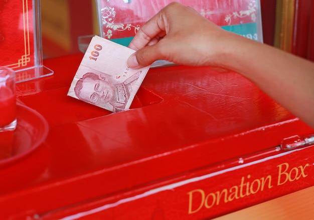 Hand van vrouw die geld voor offertory in schenkingsdoos zet