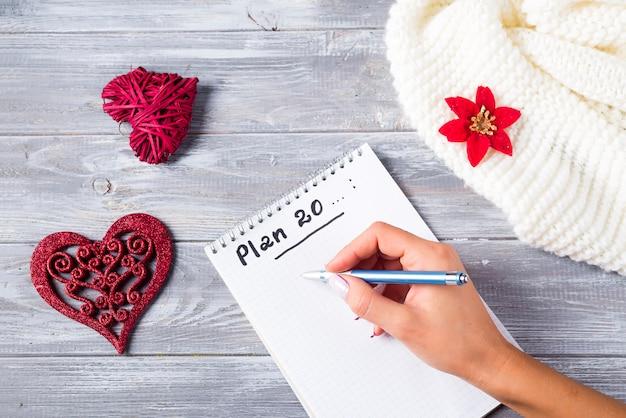 Hand van vrouw die op de groeten van blocnotekerstmis schrijven met decoratie op houten