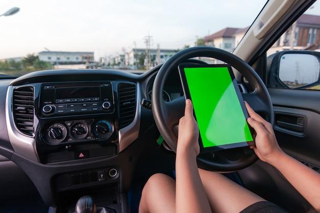 Hand van vrouw die tablet met lege groene het schermmonitor in auto suv gebruiken