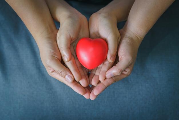 Hand van vrouw en kind die rood hart houden.