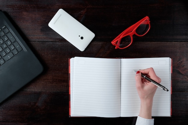 Hand van vrouw het schrijven in notaboek, bedrijfsreeks laptop de hoogste mening van glazenglazen