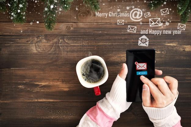 Hand van vrouw met behulp van de mobiele telefoon voor het verzenden van e-mailbericht met e-mailsymbool en enveloppictogram