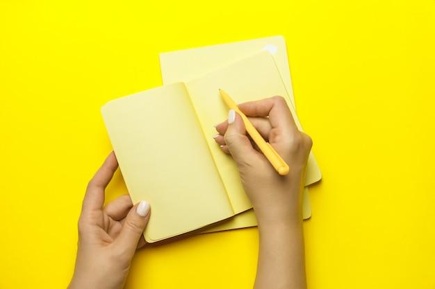 Hand van vrouw met gele pen en notitie