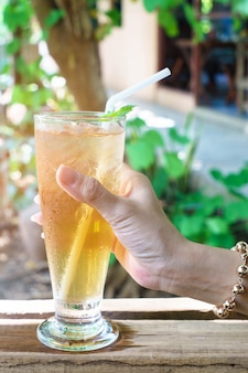 Hand van vrouw met ijs gele chrysanthemum thee met groene pepermunt in de natuur.
