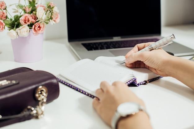 Hand van vrouw schrijven in lege blocnote geplaatst op office desktop met laptop, pot met bloemen