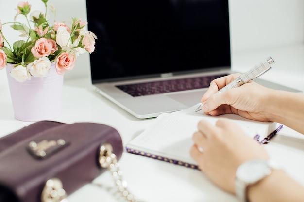 Hand van vrouw schrijven in lege notitieblok geplaatst op kantoor desktop met laptop, pot met bloemen