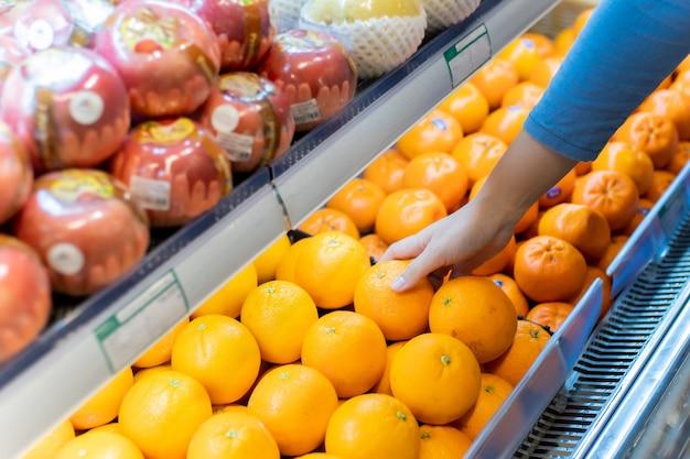 Hand van vrouw sinaasappel in supermarkt kopen