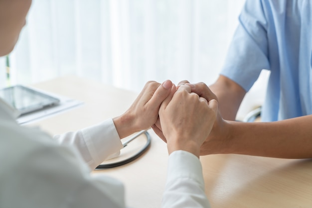 Hand van vrouwelijke artsenholding op haar hogere patiënt