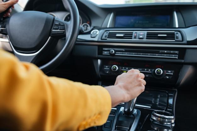 Hand van vrouwelijke bestuurder die versnellingsstok verschuift alvorens auto te drijven