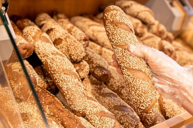 Hand van vrouwelijke klant in handschoen vers stokbrood uit broodvertoning nemen tijdens een bezoek aan de supermarkt en het kopen van voedingsproducten