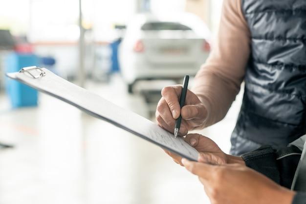 Hand van vrouwelijke technicus van autoreparatieservice die document vasthoudt terwijl mannelijke cliënt met pen zijn handtekening zet na het repareren van de auto