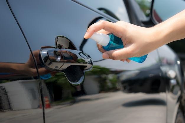 Hand van vrouwen bespuitende alcohol, ontsmettende nevel op handvat van autodeur. voorkom infectie covid-19