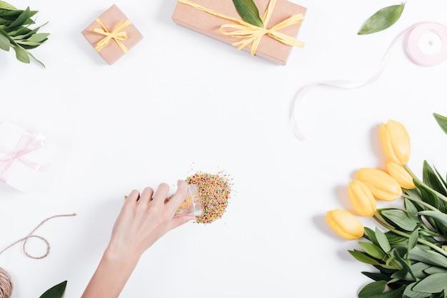Hand van vrouwen verfraaide de tafel met bloemen en dozen met geschenken en linten