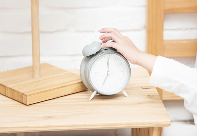 Hand van weinig aziatische wekker van de meisjesaanraking terwijl zij die op wit lui bed leggen om te ontwaken en klok te stoppen rinkelen.
