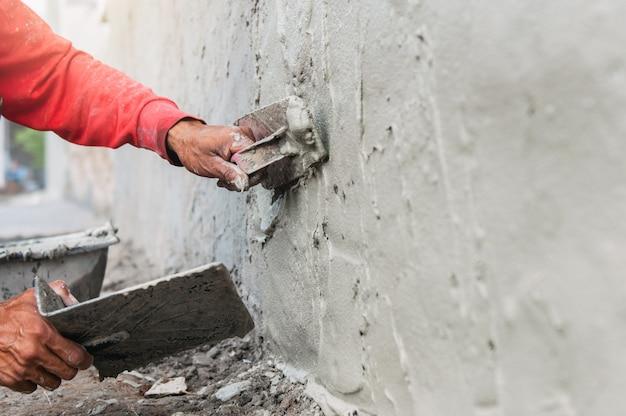 Hand van werknemer die cement aan de muur pleistert voor het bouwen van een huis op de bouwplaats