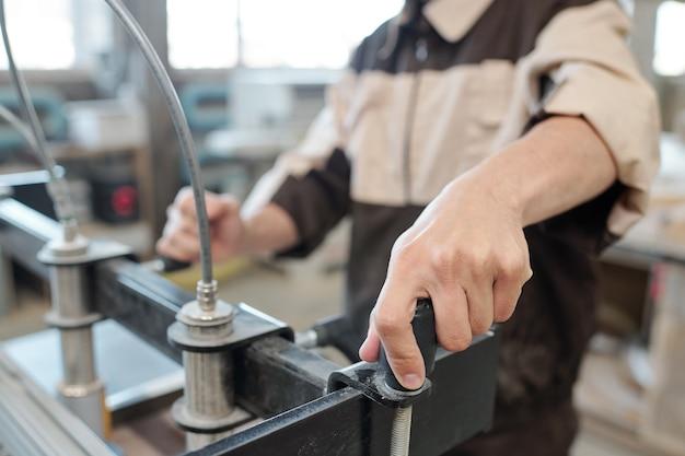 Hand van werknemer of ingenieur van eigentijds meubilair die fabrieks draaiende handgreep van industriële machine produceert terwijl het werkstuk wordt bevestigd