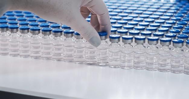 Hand van wetenschapper die kolf vasthoudt met laboratoriumglaswerk en reageerbuizen in chemisch laboratorium chemical
