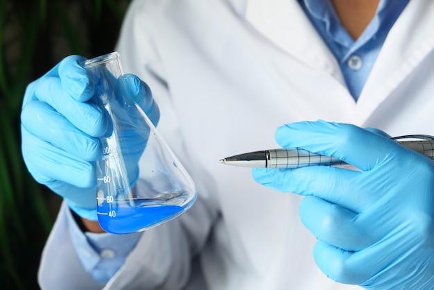 Hand van wetenschapper die laboratoriumglaswerk van boven naar beneden houdt.