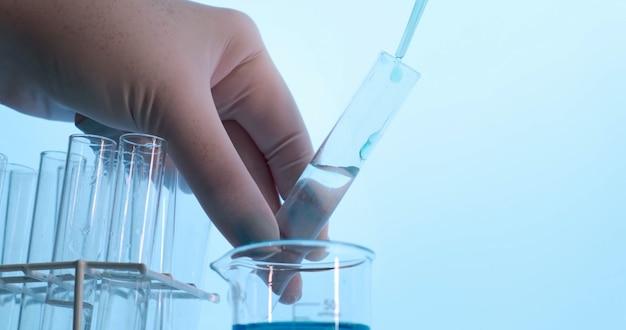 Hand van wetenschapper met kolf met laboratoriumglaswerk en reageerbuizen in chemisch laboratorium. wetenschapslaboratorium onderzoeks- en ontwikkelingsconcept. coronavirus.