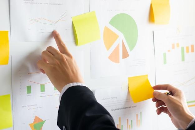 Hand van zaken die en financiële cijfers werken analyseren op een grafiek