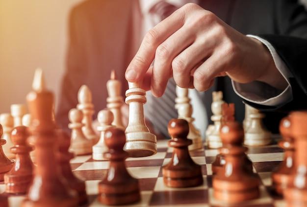 Hand van zakenman bewegend schaakcijfer in schaakspel