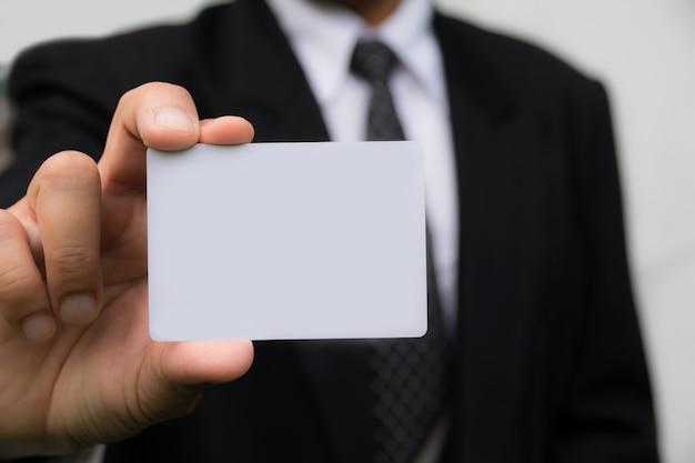 Hand van zakenman die de witte kaart op witte achtergrond houdt.