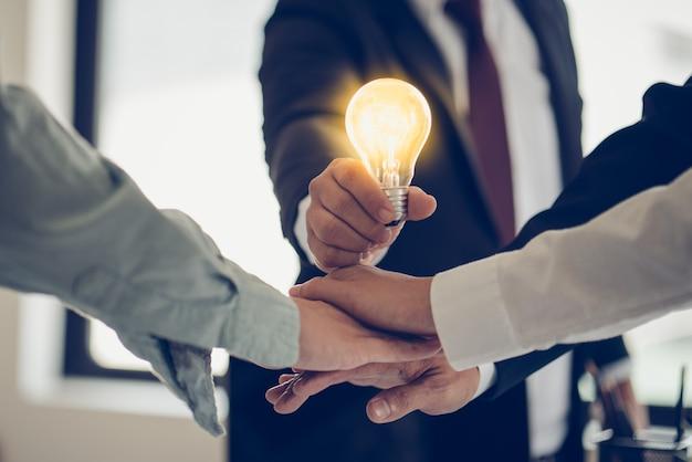 Hand van zakenman die gloeilamp als symbool van succesidee houdt