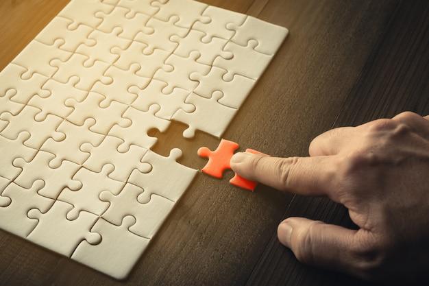 Hand van zakenman die laatste stukpuzzels, bedrijfssuccesconcept houden