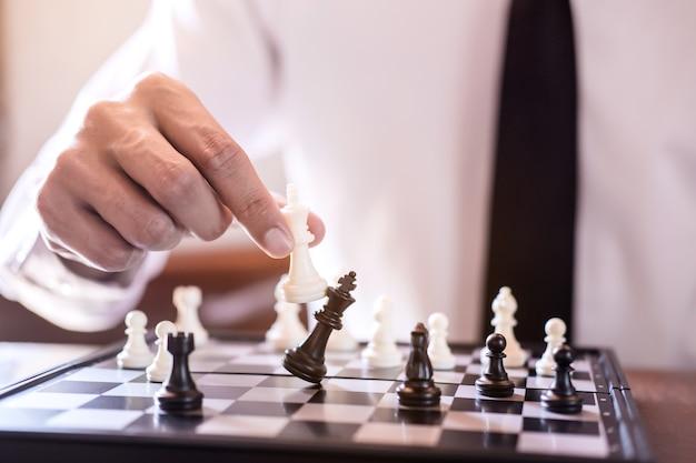 Hand van zakenman gebruik koning schaakstuk wit speelspel te omverwerpen de tegenpartij