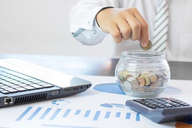 Hand van zakenman gestapelde geldmuntstukken in kruik, concept als financiën, besparing en kapitaalbankwezen