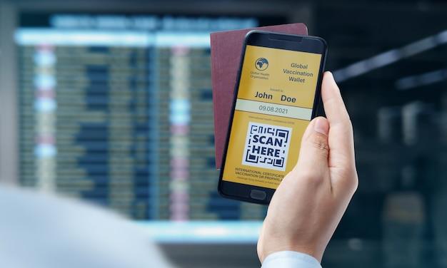 Hand van zakenman houden vaccinatiecertificaat paspoort voor reizen of zaken, covid-19 en gezondheidszorg concept.